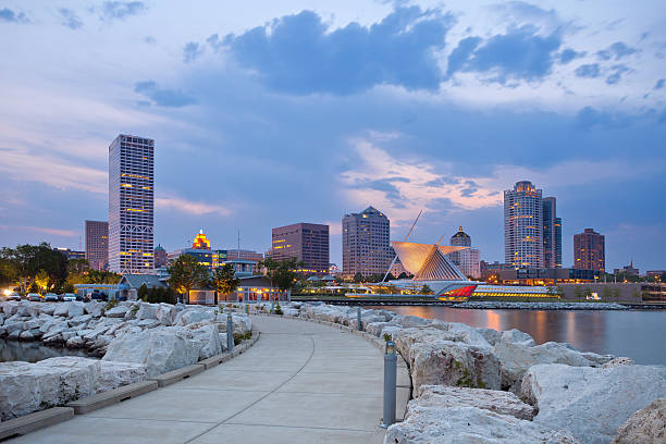 City of Milwaukee skyline. Image of Milwaukee skyline at twilight with city reflection in lake Michigan and harbor pier. milwaukee wisconsin stock pictures, royalty-free photos & images