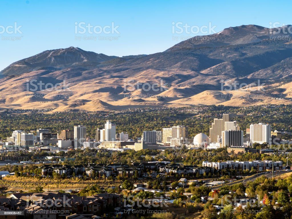 City of Reno Nevada cityscape in early autumn with hotels, casinos, apartments and mountains in the background. stock photo