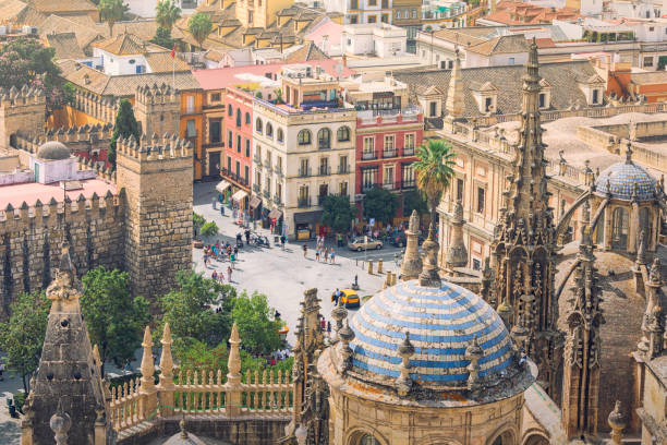 City of Seville, Spain City of Seville, in the foreground the spires and domes of Seville cathedral, in the background an old town street with people moving about. santa cruz seville stock pictures, royalty-free photos & images