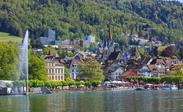 City of Zug in Switzerland Zug, Switzerland - 6 May, 2016: view of the city of Zug from Lake Zug, people on the embankment of the lake. The city of Zug is the capital of the Swiss canton of Zug. zug stock pictures, royalty-free photos & images