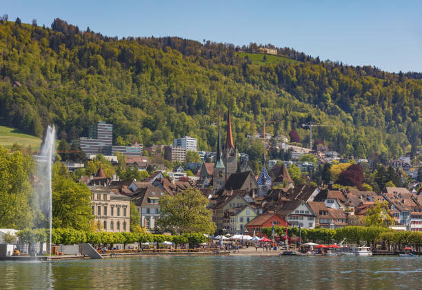 City of Zug in Switzerland Zug, Switzerland - 6 May, 2016: buildings of the city of Zug as seen from Lake Zug. The city of Zug is the capital of the Swiss canton of Zug. Lake Zug is a lake in central Switzerland, situated between Lake Lucerne and Lake Zurich. zug stock pictures, royalty-free photos & images