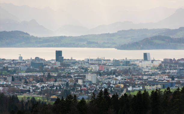 City of Zug, Switzerland Zug, Switzerland - 15 November 2015: The Swiss city of Zug and Baar with Lake Zug in the evening sunlight. Due to attractive taxes, Zug (population 29'000) and neighbouring Baar (left front, population 22'000) are popular business locations for global holdings, corporations and fintech companies. zug stock pictures, royalty-free photos & images