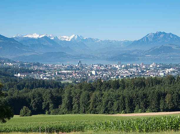 City of Zug, Switzerland, with lake Zug and mountain panorama The Swiss city of Zug with snowcapped mountains and Lake Zug in the background. Due to very low taxes, Zug is a very attractive location for global holdings and corporations. zug stock pictures, royalty-free photos & images