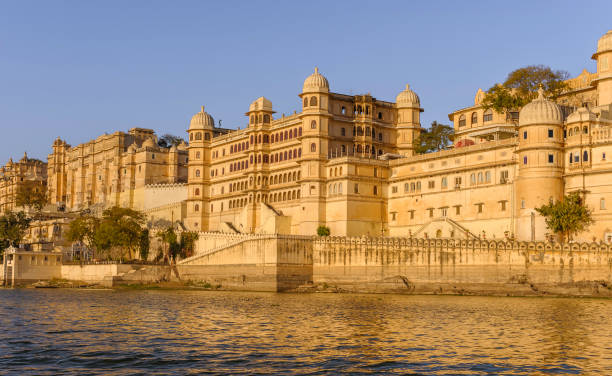City Palace and Pichola lake at sunset, Udaipur, India. Udaipur, India - February 27, 2010: City Palace (Maharajah's Palace) at sunset as viewed from Pichola lake on a beautiful winter evening on February 27, 2010, Udaipur, Rajasthan, India. lake palace stock pictures, royalty-free photos & images