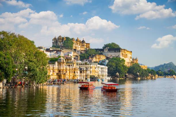 City Palace and tourist boat on lake Pichola. Udaipur, Rajasthan, India stock photo