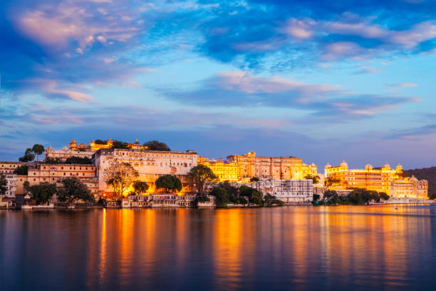 City Palace, Udaipur -  palace complex on Lake Pichola, Udaipur, Rajasthan indian tourist landmark - Udaipur City Palace complex in the evening twilight with dramatic sky - panoramic view. Udaipur, India lake pichola stock pictures, royalty-free photos & images