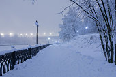 City park by the river covered in snow.