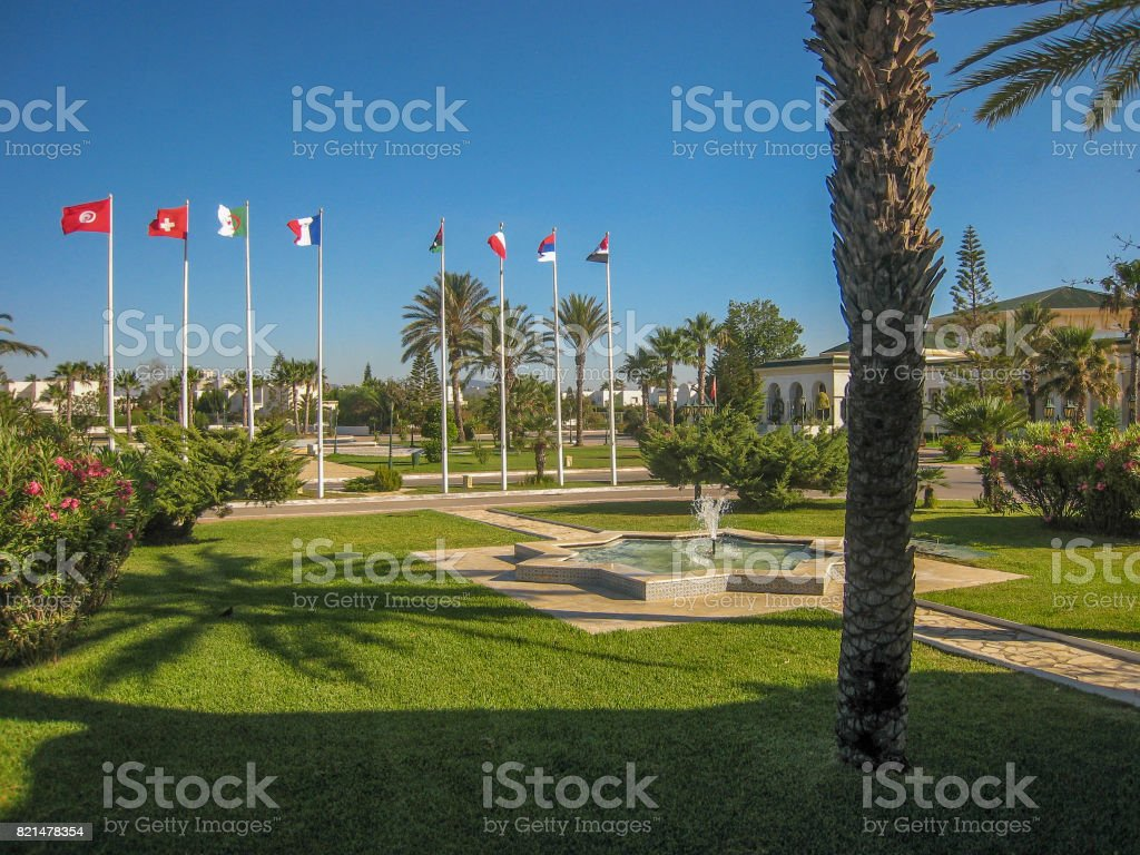 City park in Tunisia with palm trees and flags stock photo