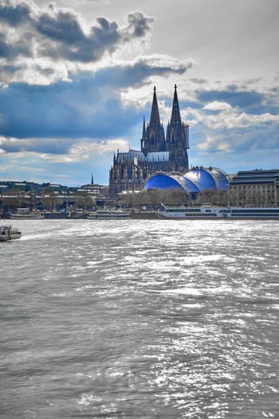 Stadtportrait Kölner Dom, Groß St Martins Kirche mit Blick über den Rhein und dem Ufer im Vordergrund mit einer wolkigen Welle und römischen Asphalt. – Foto