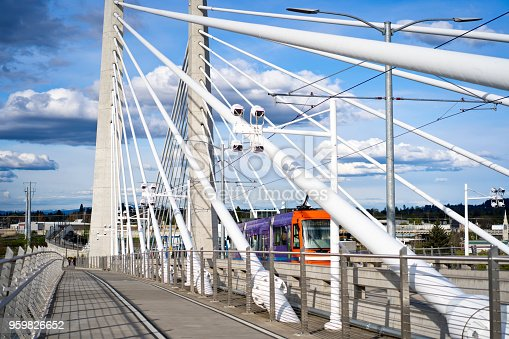 City public transport streetcar is moving along of the cables Tilikum Crossing transportation and pedestrian Bridge with concrete central columns across the Willamette River in Portland Oregon