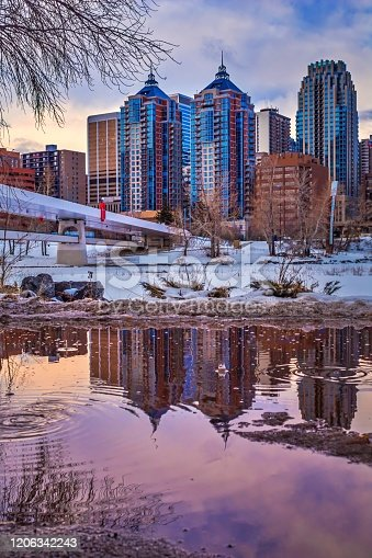 A unique view of downtown Calgary buildings reflecting into a puddle of water.