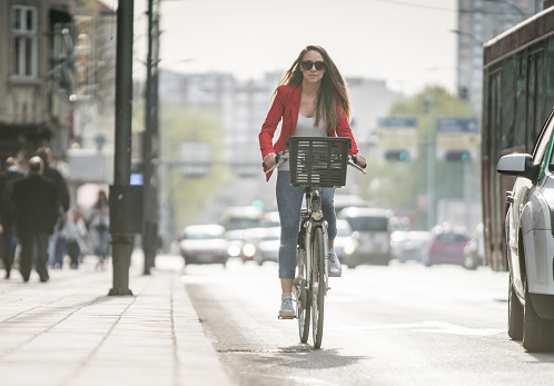 Young woman riding a bike through the city while going to work