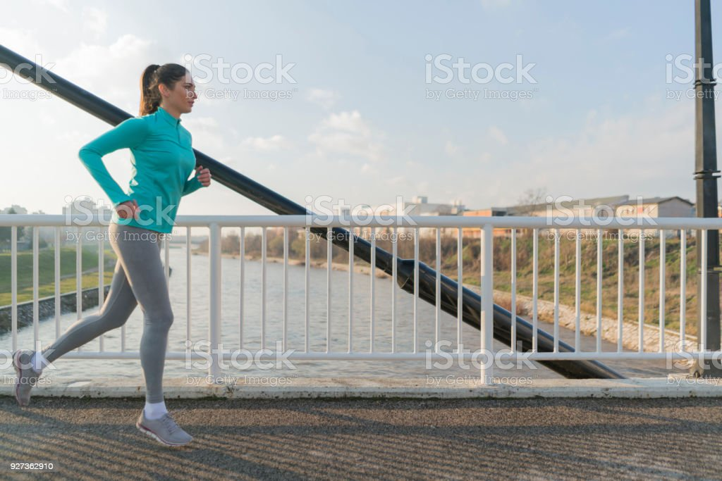 City Run Beautiful, young female athlete running across the bridge. Active Lifestyle Stock Photo