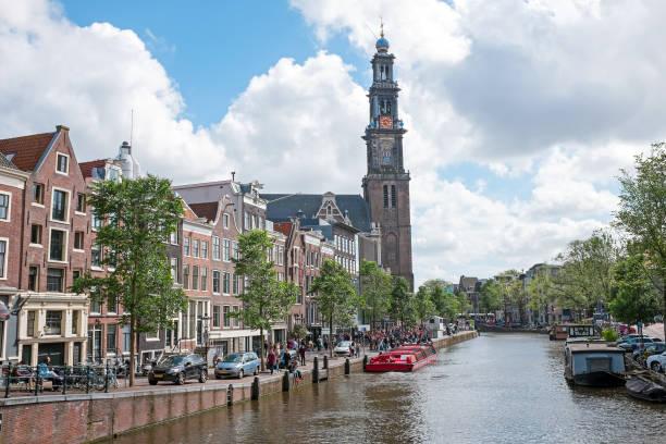 stad pittoreske in amsterdam nederland op de prinsengracht met de westerkerk - westerkerk stockfoto's en -beelden