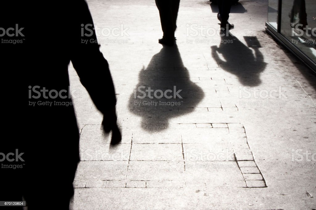 City shadows and silhouettes Blurry silhouettes and shadows of people walking on the city sidewalk Abstract Stock Photo