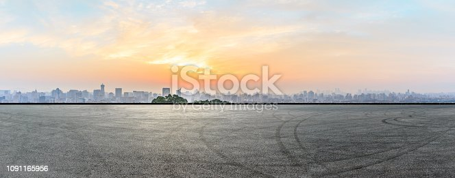 613763122 istock photo City skyline and buildings with empty asphalt road at sunrise 1091165956