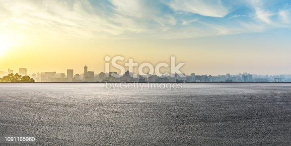 613763122 istock photo City skyline and buildings with empty asphalt road at sunrise 1091165960