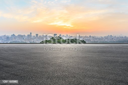 613763122 istock photo City skyline and buildings with empty asphalt road at sunrise 1091165980
