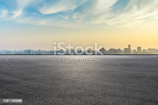 istock City skyline and buildings with empty asphalt road at sunrise 1091165998
