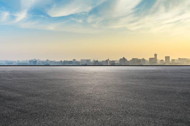 horizonte de la ciudad y edificios con carretera de asfalto vacío al amanecer - vía fotografías e imágenes de stock