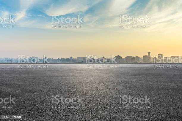 Photo of City skyline and buildings with empty asphalt road at sunrise