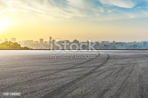 613763122 istock photo City skyline and buildings with empty asphalt road at sunrise 1091166002