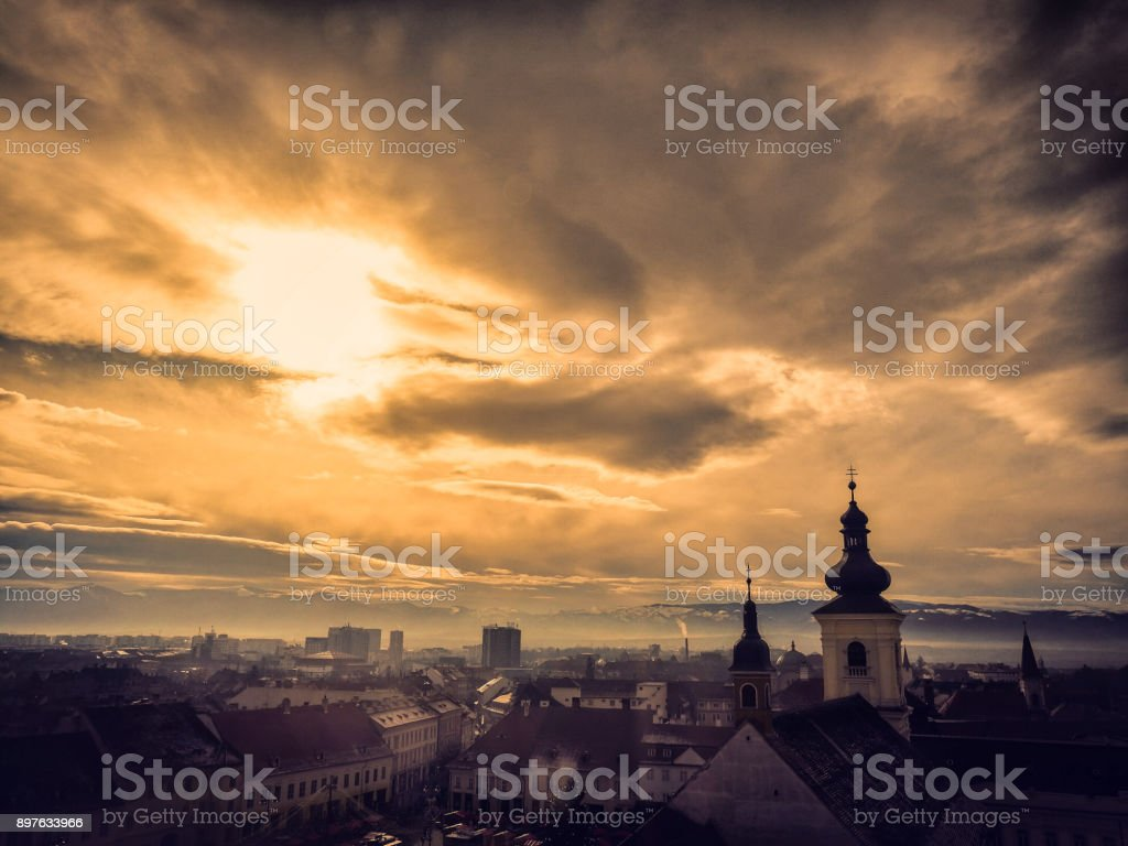 City skyline of Sibiu, Transylvania, Romania with church spires and snowy Carpathian mountains in distance stock photo