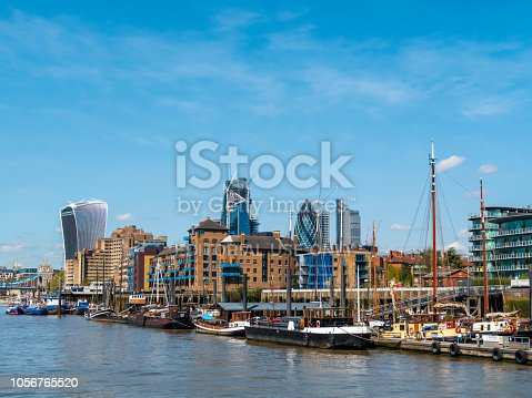 City of London skyscrapers, including 'The Walkie-Talkie' and 'The Gherkin', behind a collection of old boats moored beside the River Thames near St Katharine Dock and Tower Bridge. The boats are part of Hermitage Community Moorings (HCM), a co-operative which builds, owns and operates the moorings. Some of the boats are long-term residential 'floating homes' while some are visiting. (Incidental people.)