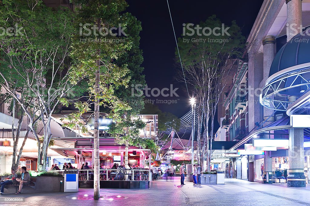 City street and trees  illuminated with lights at night stock photo