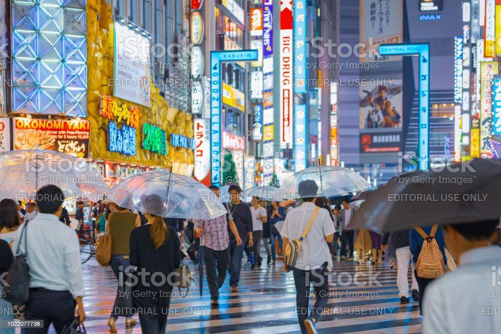 City street night life while rainy season, crowd people holding...