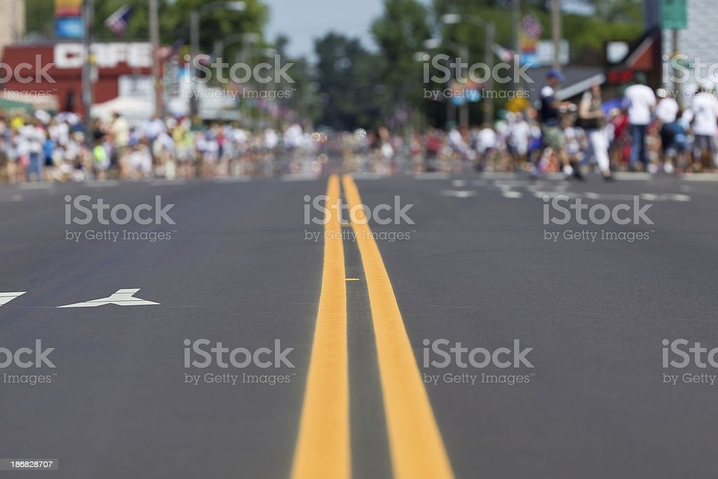 A city street lined with defocused people waiting the start of a...