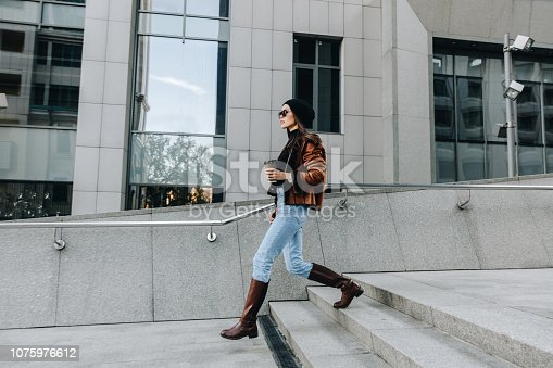 istock City style. Coffee break. Autumn/spring. Stylish girl in casual clothes is walking outdoors with a cup of coffee 1075976612