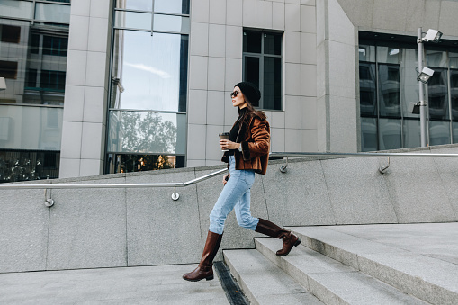 City style. Coffee break. Autumn/spring. Stylish girl in casual clothes is walking outdoors with a cup of coffee