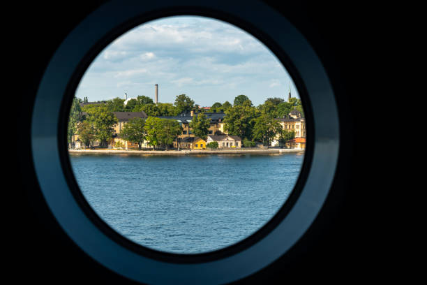 City summer landscape view of Stockholm seen from inside a ship cabin with round peep-hole window. stock photo
