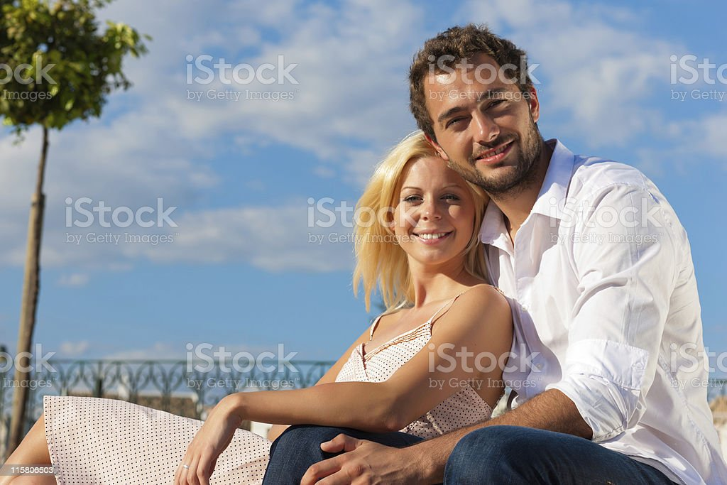 City tourism - couple in vacation on a bench royalty-free stock photo