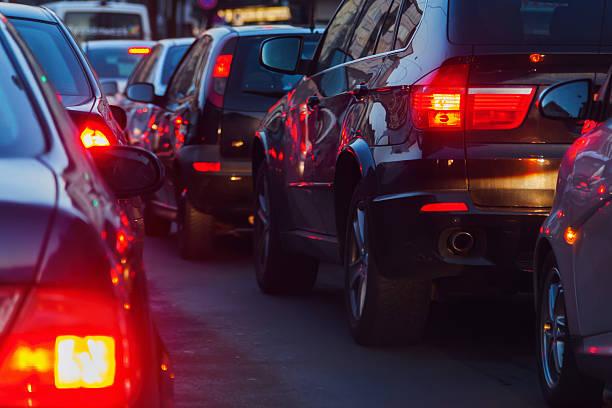 traffico in città al tramonto - queue foto e immagini stock