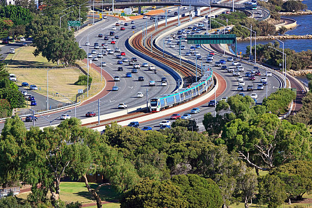 City transport: electric train travels down middle of busy freeway Efficient city transit: TransPerth metro electric train travels unimpeded along the median strip of the busy Kwinana Freeway.  Running on the 25kV electrified Mandurah Railway Line, the train is approaching the Perth CBD.  Train is pictured rounding S curves on approach to the Narrows Bridge.  Horizontal. electric train stock pictures, royalty-free photos & images