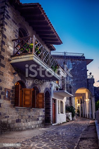 City view after the sunset with a beautiful old house with window blinds opened and a balcony full with flowers in the city of Samothraki on Samothrace Island in Greece against a blue sky