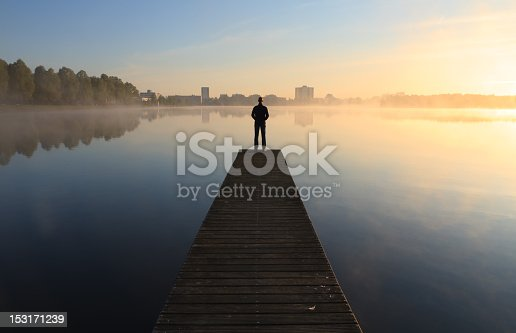 Man looking over a foggy lake toward the city during sunrise.