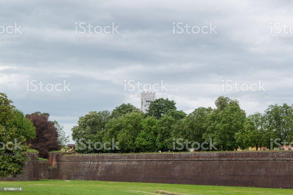 Stadtmauer von der italienischen Stadt Lucca in der Toskana mit Bäumen und den Turm des Doms – Foto