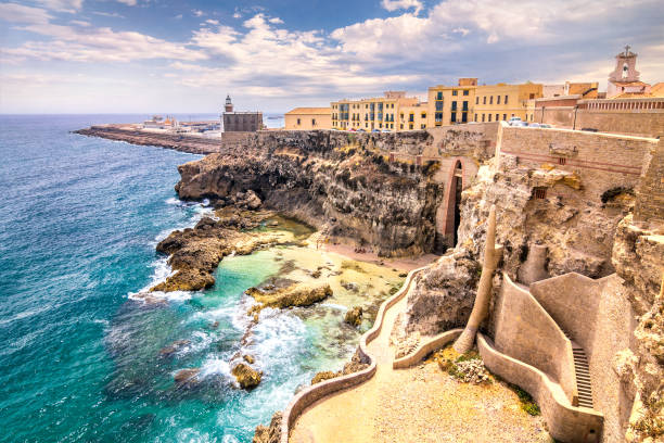 city walls, lighthouse and harbor in melilla. - north africa stock photos and pictures