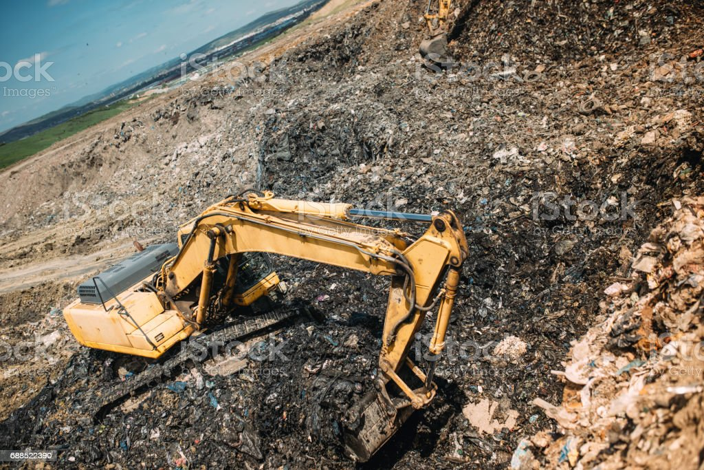 city waste on dumping grounds. Details of industrial excavators working, digging and loading stock photo