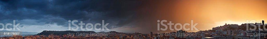 Cidade com um céu dividido pôr-do-sol e chuva forte - foto de acervo