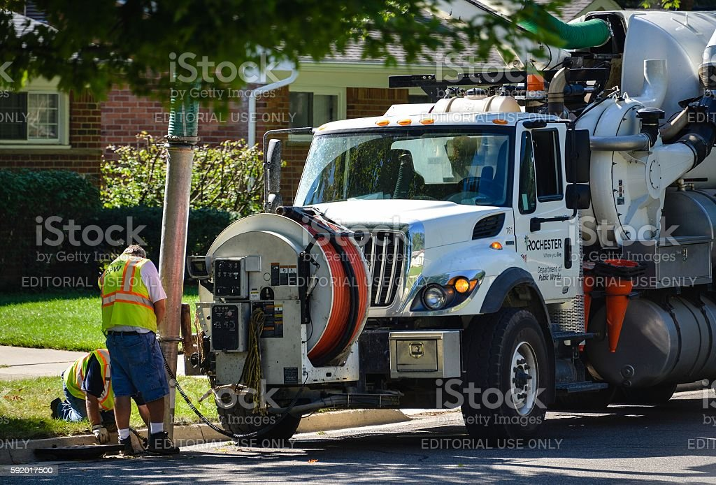 City Workers Cleaning Sewer stock photo