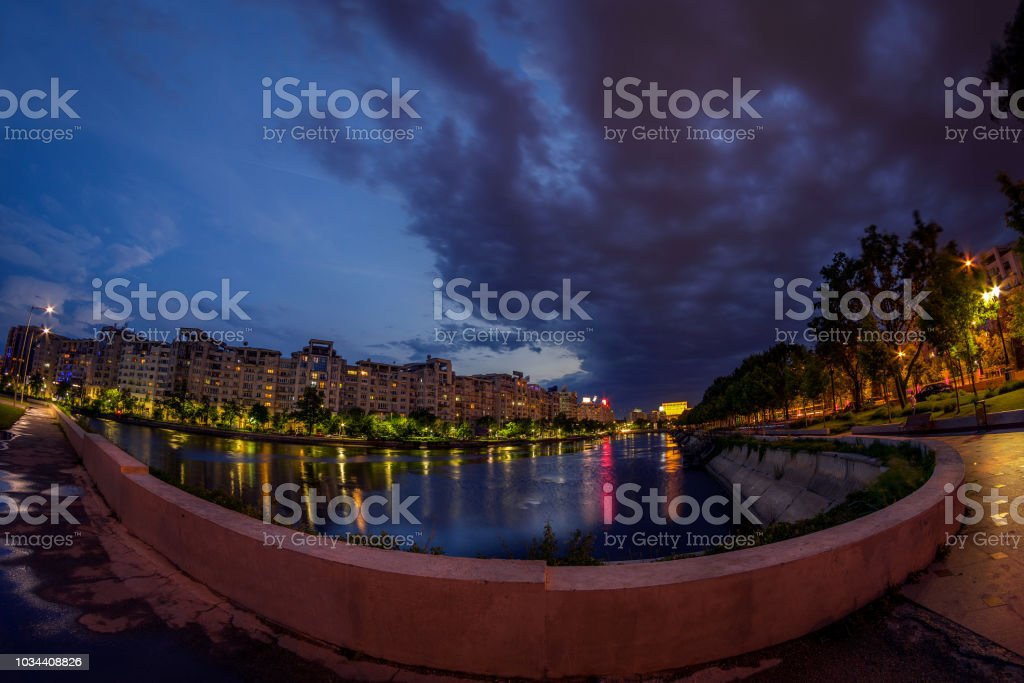 Cityscape after sunset before a heavy storm with reflection in the river and buildings stock photo