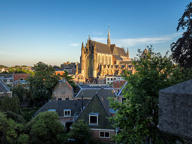 cityscape and church in Leiden, Netherlands Aaerial view on the roofs of the old town and gothic brick church, Hooglandse Kerk, in Leiden, The Netherlands at sunset leiden stock pictures, royalty-free photos & images