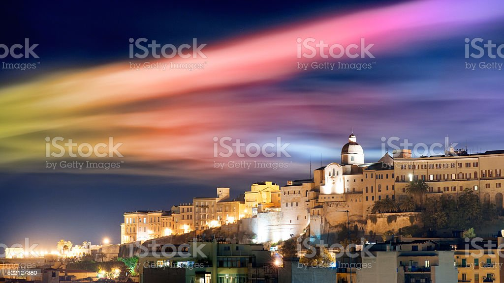 Cityscape by night with colored smoke in the sky stock photo