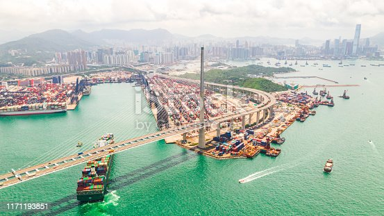 Cityscape drone aerial view of Hong Kong city, port industrial district, cargo container ship, cranes, car traffic on Stonecutters bridge. Logistic industry or freight transportation business concept