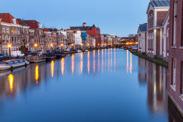 Cityscape - evening view of the city canal with bridge and boats Cityscape - evening view of the city canal with bridge and boats, the city of Leiden, Netherlands leiden stock pictures, royalty-free photos & images