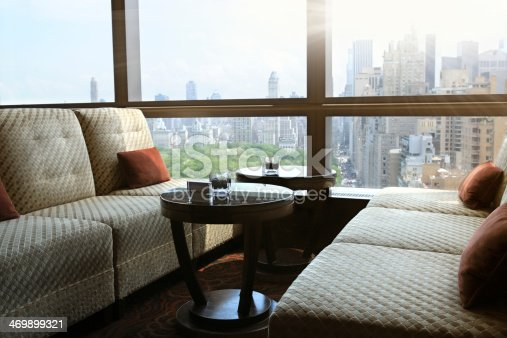Table and sofa close to a window inside a cafe. On the table there are flower in a bowl. Out of the window there is a panoramic view of Central park and Upper Midtown Manhattan, NYC.